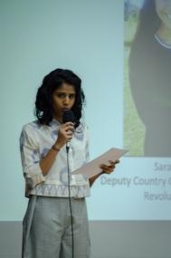 Tulasi introducing speaker Sara Mahdi. Photo credit: Beheld